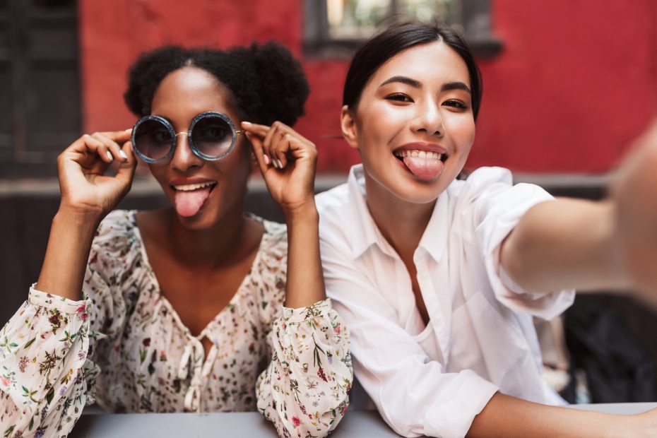 Two pretty girls happily showing tongues while taking photos tog